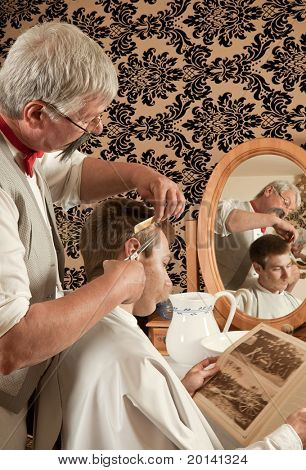 Barber cutting the hair of a customer in an antique victorian barbershop (the antique magazine is from 1910).