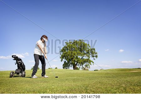 Active senior female golf player with golf bag concentrating to hit the ball with driver on fairway on beautiful golf course with blue sky in background.