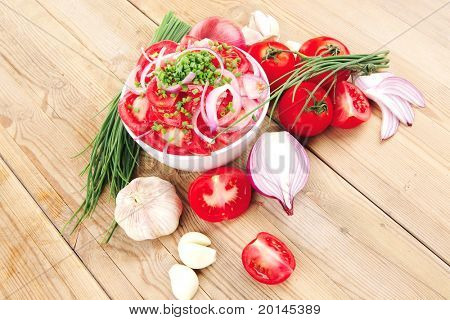 vegetable food : fresh tomato salad in white bowl with bundle of chives and raw tomatoes on twig over wooden table