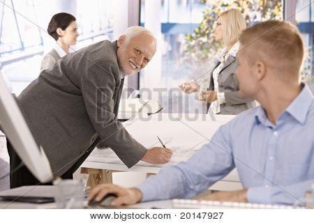 Senior Architect bei der Arbeit, lächelnd bei jüngeren Kollegen mit Team im Büro.?