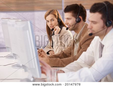 Attractive young female customer servicer working in callcenter.?