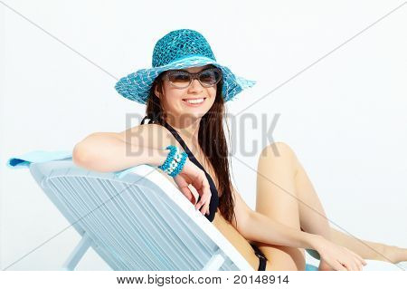 Portrait of a young girl sitting in chaise lounge, looking at camera and smiling