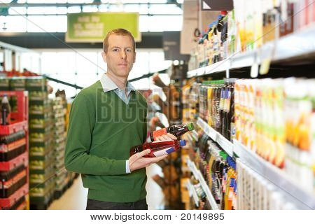 Portrait of a man comparing two products in a grocery store