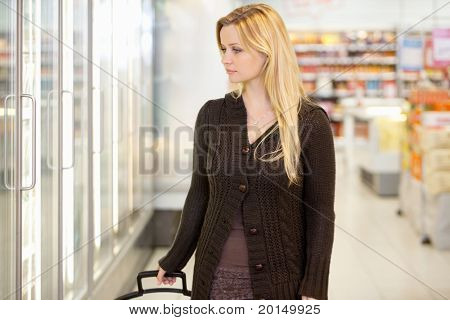 Young woman looking at goods in refrigerator section of supermarket
