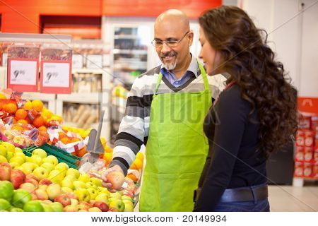 A woman buying groceries receiving help from a store clerk