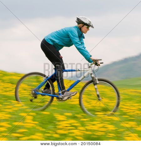 Spring bike riding - woman downhill on bike in dandelion (intentional motion blur)