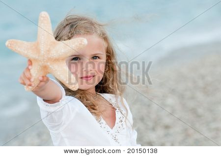 Sommerferien - schönes Mädchen mit Seestern am Strand