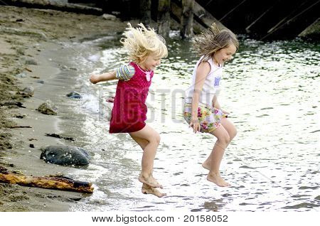 Vacation - children jumping in the water with bare feet