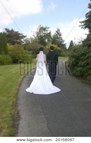 bride and groom with trailing veil walking into the future
