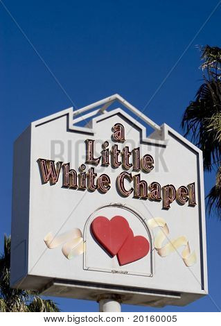 vegas wedding chapel sign against colbot blue sky with palm trees at both sides