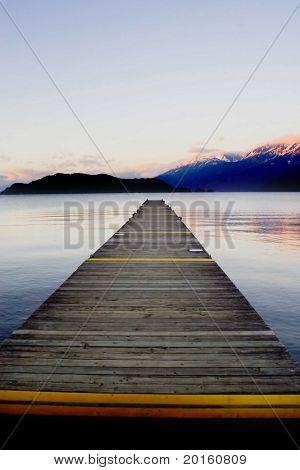 plank pier extending over calm water