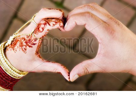 ceremonial wedding hands in shape of heart one male one female coming together to form heart