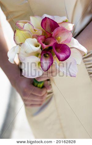 beautiful calla lillies on silk dress with hands wedding bouquet detail