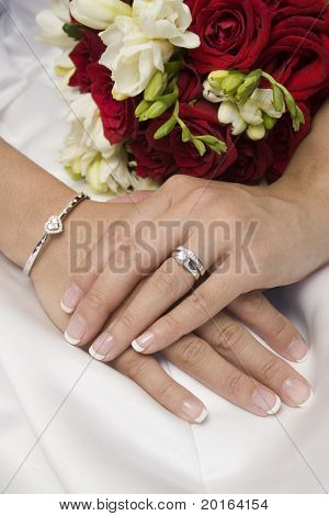 bride's hands sitting on lap with bouquet in background