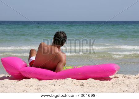 Handsome Man Taking A Sunbath At The Beach.