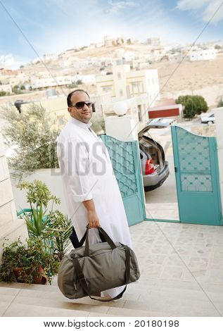 Saudi arabic businessman traveling with his car, holding a bag on stairs