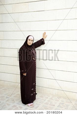Muslim woman beside white wall, vertical photo good for your text or message