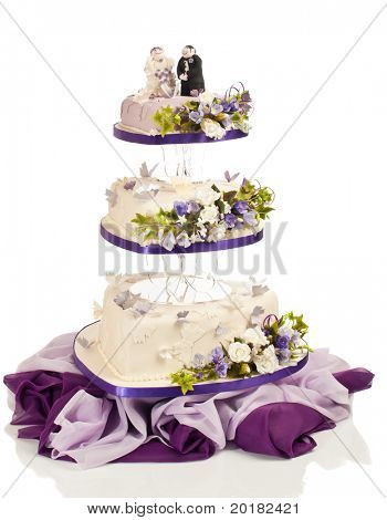 Heart shaped wedding cake in three tiers with flowers and butterflies made from sugar icing on white background