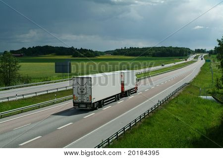 lorry driving late in the evening, on long stretch of highway
