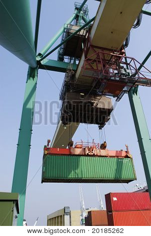 container being transported through air by crane