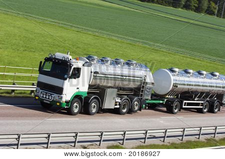 oil-tanker, truck on highway against green countryside
