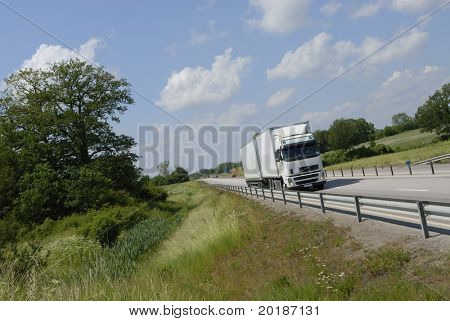 white lorry driving in the countryside