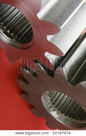 two gears connecting against red background