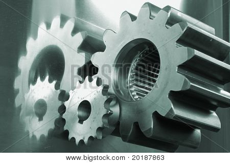 gears and pinions with reflection in a greenish cast