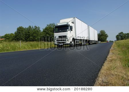 clean white truck driving, surrounded by countryside