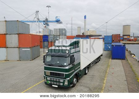 truck waiting in port for cargo, with cranes and containers