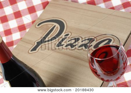 pizza-box, wine-bottle and glass against red/white cloth