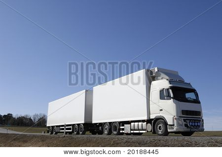 white truck driving on country-road under blue sky
