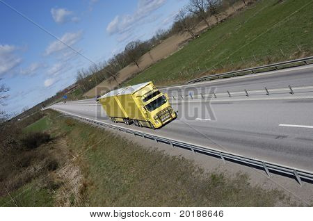 yellow truck driving on long straight of highway surrounded by country-side