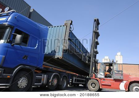 large forklift hoisting container from stationary truck