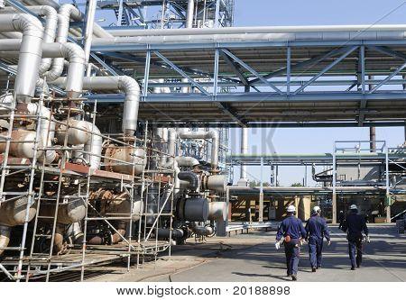 people leaving work inside oil-refinery