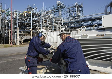 two engineers working on pump inside refinery