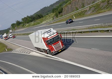 red and white truck speeding on highway, elevated frontal view