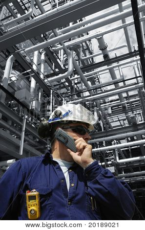 engineer talking in mobile-phone with blue-toned pipelines in background