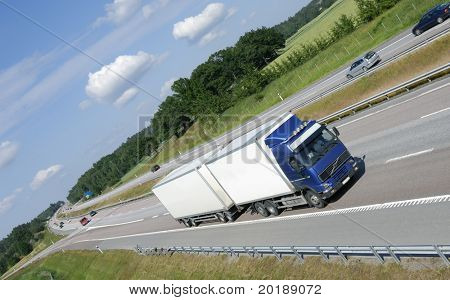 blue white truck driving on highway