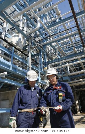 engineers inside oil-refinery with pipelines in background