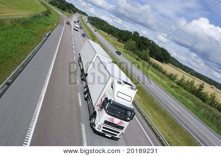 giant white truck on highway, extreme wide-angle and tilted horizon to induce speed