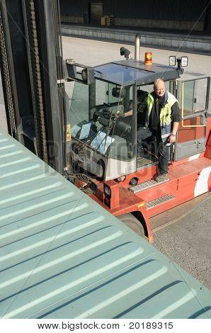 forklift truck hoisting container with driver getting in