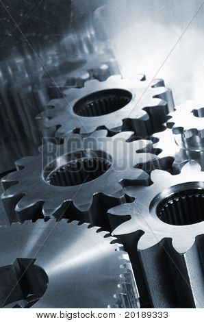 gear machinery mirrored in titanium background and in a blue toning concept