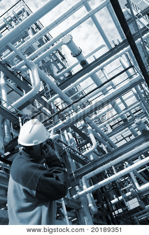 engineer in hard-hat standing in front of large pipeline construction inside oil refinery