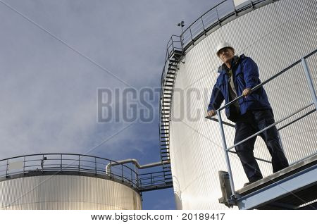 engineer standing in front of oil-storage-tanks, tilted perspective