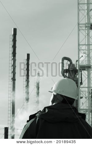 refinery with gas clouds, pipelines and pipes, with engineer in foreground, all in a greenish toning idea