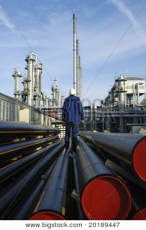 engineer standing on pipes overlooking refinery in background, powerful depth-of-field