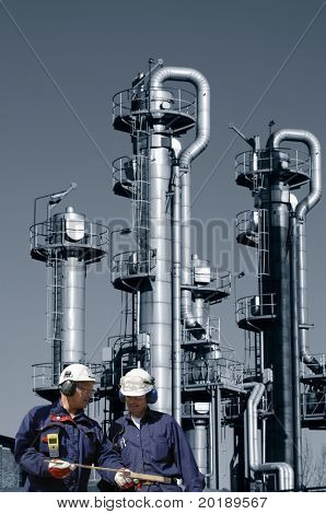 two engineers in hard-hats, standing in front of oil and gas refinery