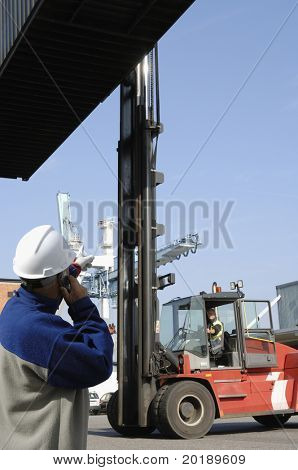 large forklift hoisting container with engineer directing from ground