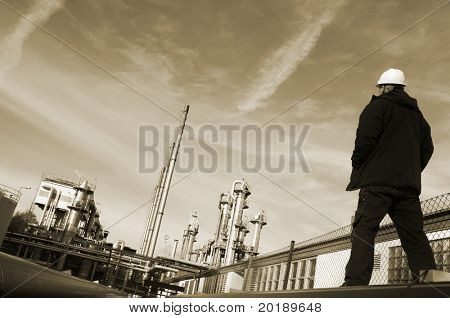 engineer wearing hard-hat overlooking large oil and gas refinery, brownish toning concept